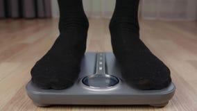 Mannen i svart slår att kontrollera vikt på elektronisk skala med skärm lager videofilmer