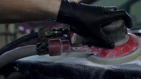 Mannen i svarta handskar arbetar med luftslipmaskinen på service för bilkropp, closeup stock video