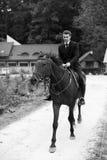 Mannen i tillbaka dräkt rider en häst längs vägen Royaltyfri Foto