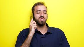 Mannen i tillfällig blå skjorta talar på telefonen över en gul bakgrund stock video