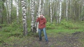 Mannen i tillfällig kläder gör stridighetkampsporter på en skogglänta, ultrarapid lager videofilmer
