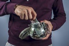Mannen i tröja tar ut dollar från moneybox Arkivfoton