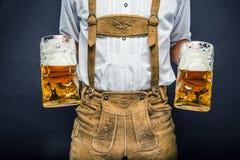 Mannen i traditionellt rymma för bavariankläder rånar av öl fotografering för bildbyråer