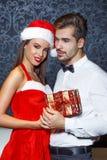 Mannen i tux får julgåva från flickvän royaltyfri bild