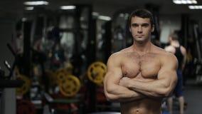Mannen, idrottsman nen, den personliga instruktören med den stål- ögonkastet och den stängda ställingen står i idrottshallen arkivfilmer