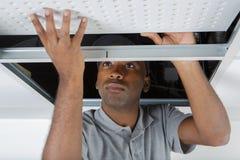 Mannen installerar det inställda taket i hus royaltyfri fotografi