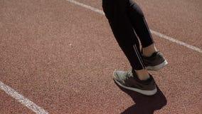 Mannen joggar på en stadionlöparbana arkivfilmer