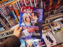 Mannen köper stor festtidskriften med Emmanuel Macron och hans fru Brigitt Arkivbilder