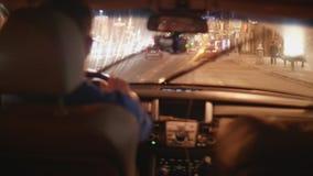 Mannen kör bilen i afton i Moskva på vägen med julgarneringar stock video