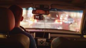 Mannen kör bilen i trafikstockning i afton Suddig sikt av stadsljus arkivfilmer