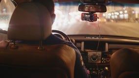 Mannen kör bilen i trafikstockning i afton Suddig sikt av stadsljus stock video