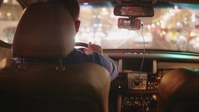 Mannen kör bilen i trafikstockning i afton Suddig sikt av stadsljus lager videofilmer