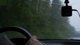 Mannen kör en bil i regnigt väder arkivfilmer