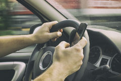 Mannen kör en bil och ett innehav en mobiltelefon fotografering för bildbyråer