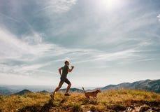 Mannen kör med hans beaglehund på bergöverkant Arkivfoton