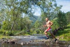Mannen kör ner en bergflod Arkivbilder
