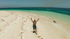 Mannen kör på en sandig strand på semester stock video