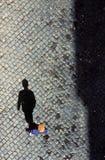 Mannen kastar en skugga på kullerstenstenen Arkivbilder