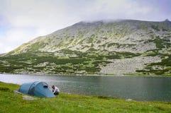 Mannen kastar ett tält i berg Royaltyfria Bilder