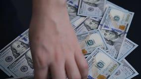 Mannen kastar på tabellen 100 dollarräkningar lager videofilmer