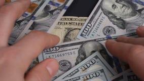 Mannen kastar på tabellen 100 dollarräkningar arkivfilmer