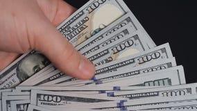 Mannen kastar på tabellen 100 dollarräkningar stock video