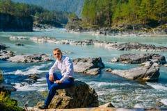 Mannen klädde affärskläder som sitter på, vaggar vid floden och bergen royaltyfria foton