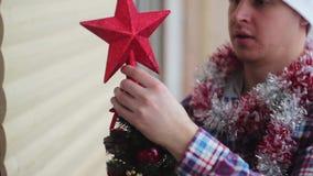 Mannen klär den härliga lilla glödande julgranen stock video