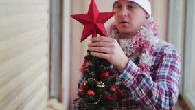 Mannen klär den härliga lilla glödande julgranen arkivfilmer