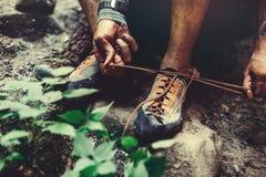 Mannen klär klättringskor för att klättra, närbild Extremt begrepp för utomhus- aktivitet för hobby arkivfoton