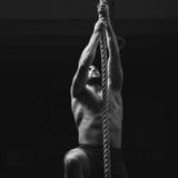 Mannen klättrar ropa på idrottshallen Arkivbild