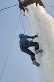 Mannen klättrar uppåt på isklättringkonkurrens Arkivfoton