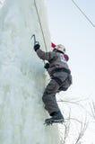 Mannen klättrar uppåt på isklättringkonkurrens Royaltyfri Foto