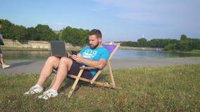 Mannen klarar av data från smartphonen till bärbara datorn som ligger på sunbed arkivfilmer