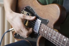 Mannen klinkar ackordet på gitarren Arkivfoton