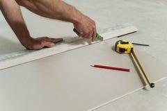 Mannen klipper av ett stycke av drywallen Arkivbilder
