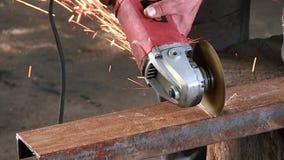 Mannen klipper en rostig metallstråle, genom att använda en rund turbin Har den slowmotion närbilden för vinkelmolar ljudet arkivfilmer