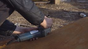 Mannen klipper ett stycke av järn med en såg för metall lager videofilmer
