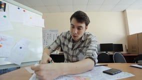 Mannen klipper försiktigt karbonpapper med den svarta orienteringen av byggnad på den arkivfilmer