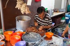 Mannen klipper griskött för rishavregröt royaltyfri fotografi