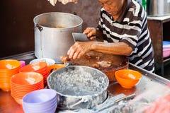 Mannen klipper griskött för rishavregröt arkivfoton