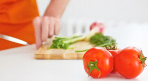 Mannen klipper mogna grönsaker på ett träbräde i bakgrunden Tre mogna tomater i förgrunden Royaltyfri Bild