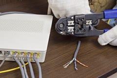 Mannen klipper nätverkskabeln, modemet på tabellen, routeren, nätverkskabeln, ett närbildmodem royaltyfri foto