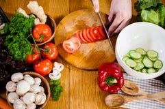 Mannen klipper nya vårgrönsaker royaltyfria bilder