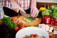 Mannen klipper nya vårgrönsaker royaltyfri fotografi