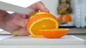 Mannen klippte med en kniv en orange frukt i nya söta och smaksatta skivor lager videofilmer