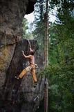 Mannen klättrar på vaggar Framgångklättring som når det bästa adrenalinet, styrka, ambition Arkivbilder