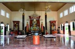Mannen knäfaller och ber på den kinesiska buddistiska templet Royaltyfri Foto