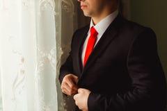 Mannen knäppas upp hans svarta omslag, medan stå för fönstret Royaltyfri Foto