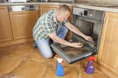Mannen knäfaller på golvet i köket och gör ren ugnen Arkivfoto